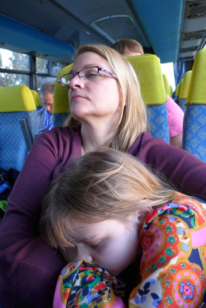 Zoë resting with her mom on the bus